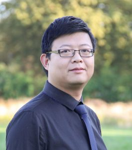 Jianwei Li, head and torso, photograph in front of trees