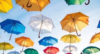 Värikkäitä sateenvarjoja sinisellä taivaalla