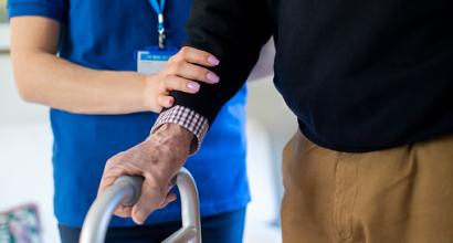 Hoitaja auttaa iäkästä henkilöä