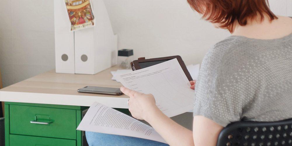 Nainen selaa pöydän ääressä papereita
