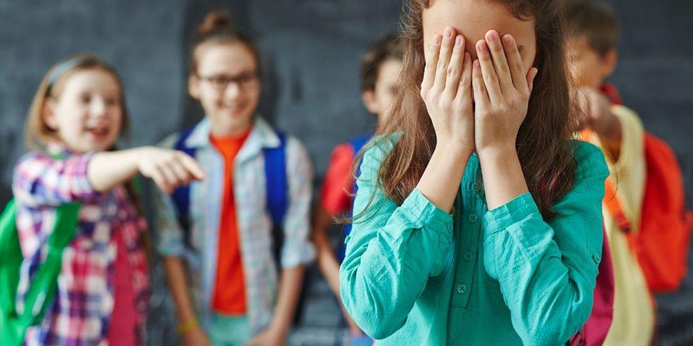 Tyttö seisoo koululuokassa kädet silmillä, takana on neljä lasta, joista yksi osoittaa häntä sormella