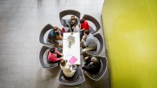 Kuvassa on 7 Brahea-keskuksen työntekijää, jotka istuvat pyödän ympärillä tekemässä töitä.
