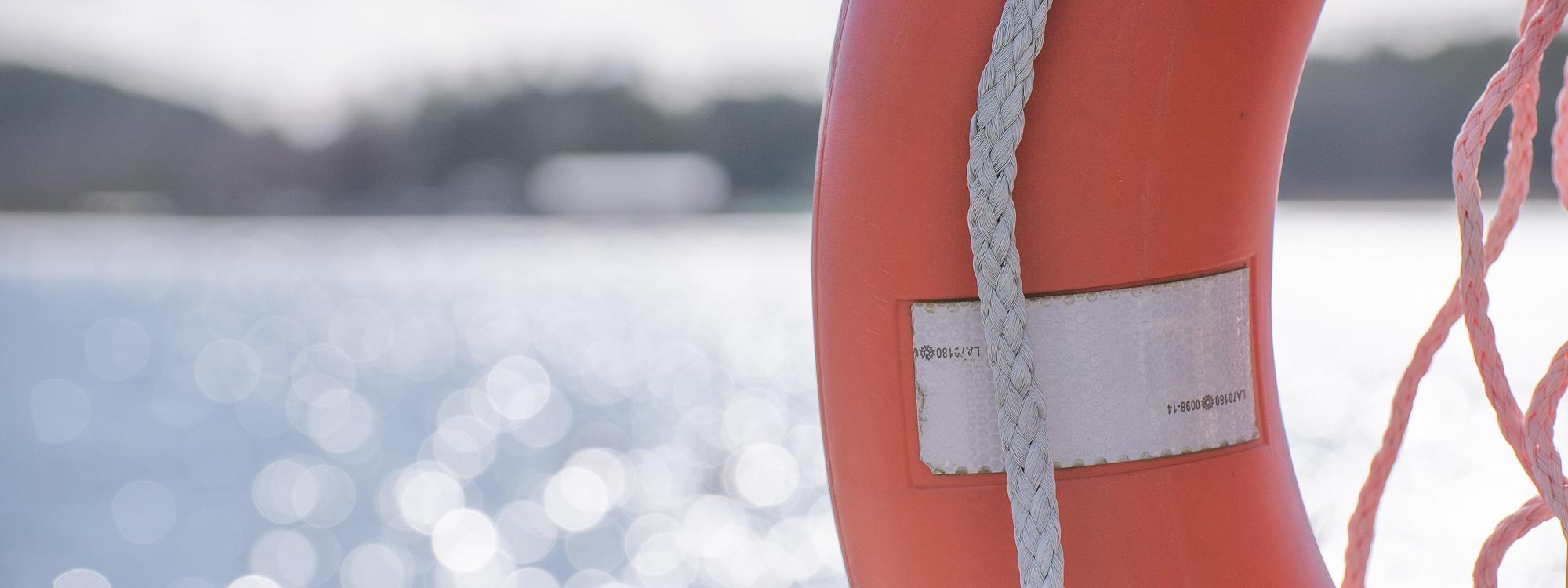 Edustalla on oranssi pelastusrengas, taustalla kimmeltää meri ja siintää rantaa sekä rakennuksia