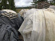 Maatalousmuoveja kerättynä suuriksi kasoiksi pihalla.