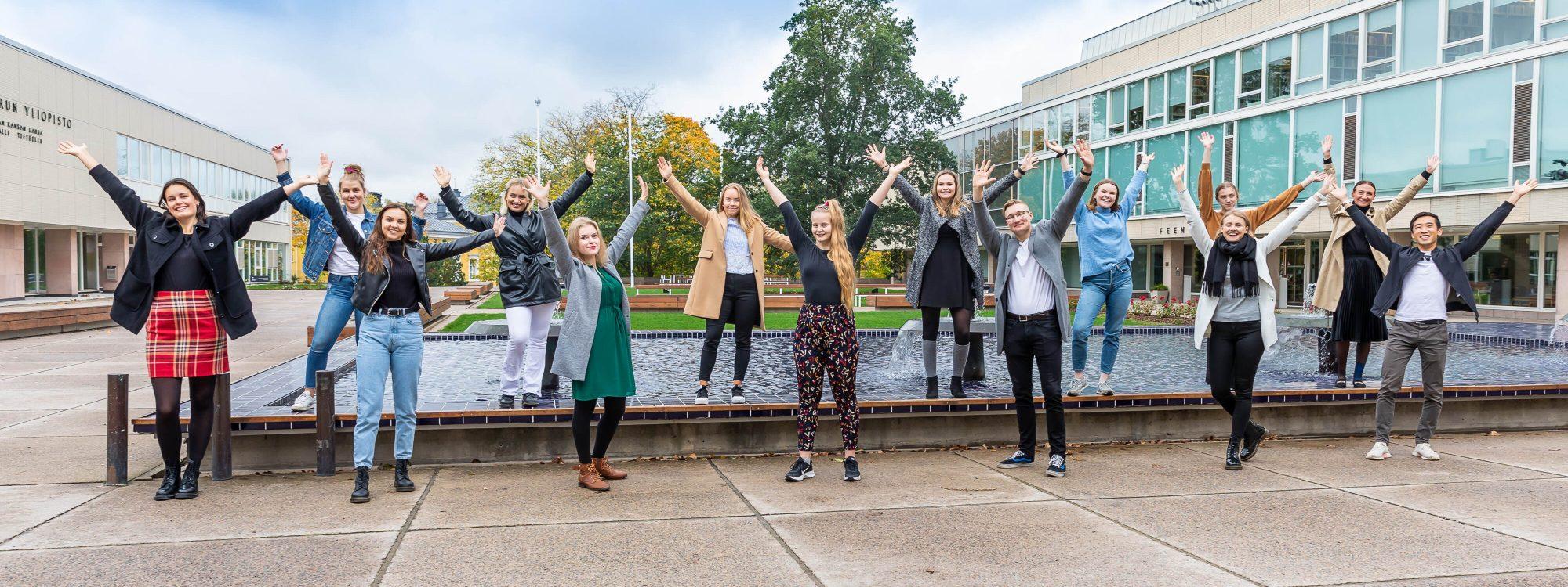 Opiskelijalähettiläät hyppäävät ilmaan Turun yliopistonmäellä suihkulähteen edessä.