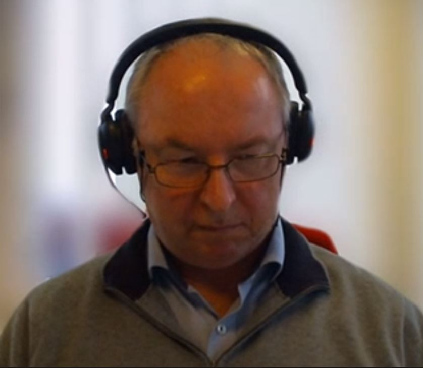 Photo of a man with headphones in an online meeting