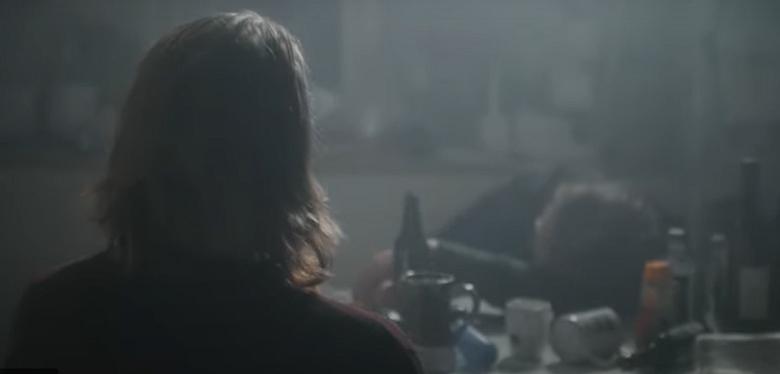 nuori ihminen etualalla katsoo sammunutta miestä, pulloja pöydällä