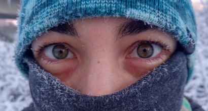 Student wearing a winter hat and a neck warmer pulled up over her nose. Only her eyes are visible.