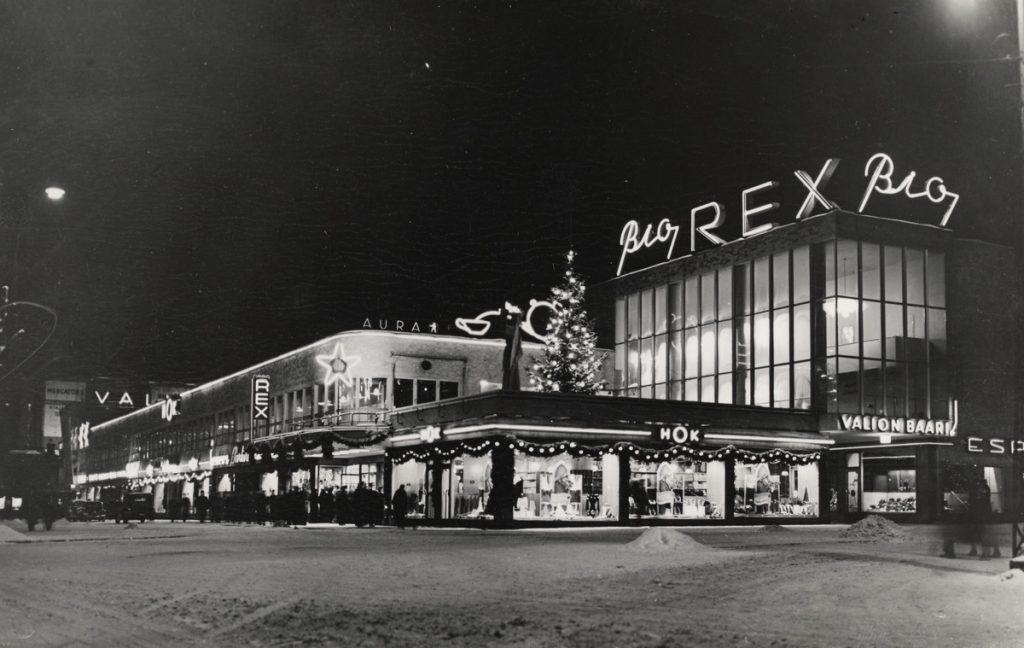 Mustavalkoinen kuva Bio Rexistä talvisena pimeänä iltana. Rakennusten ikkunoista loistaa valoa, ja kuvan keskellä on valaistu joulukuusi.