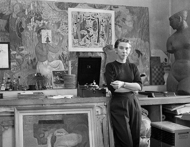 Tummaan paitaan ja tummiin housuihin pukeutunut Jansson nojaa kädet puuskassa ateljeensa pöytään. Taustalla on monenlaista taidetta: freskoja, maalauksia ja veistos.