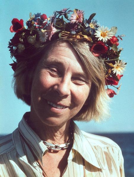 Kesäisessä kuvassa hymyilevä Jansson katsoo suoraan kameraan. Hänellä on päässään runsas kukkaseppele. Hiukset ovat vaaleat ja lyhyet. Taustalla on meri.