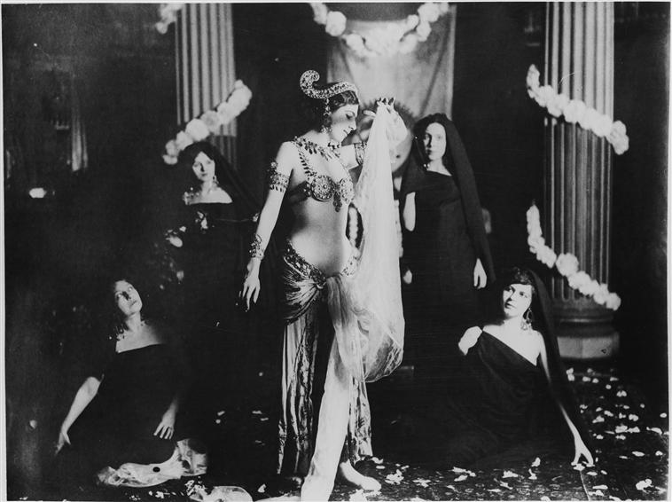 Kuvan keskellä seisoo koristeelliseen esiintymisasuun pukeutunut Mata Hari. Hänellä on runsaasti koruja, niukka yläosa ja pitkä hame sekä kädessään liina. Mata Harin ympärillä on neljä hunnutettua mustiin pukeutunutta naista, jotka kaikki katsovat häntä.