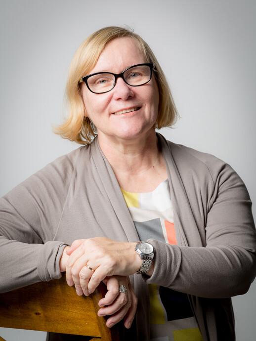 Potrettikuva Kirsi Vainio-Korhosesta. Professori istuu tuolilla ja katsoo hymyillen kameraan.