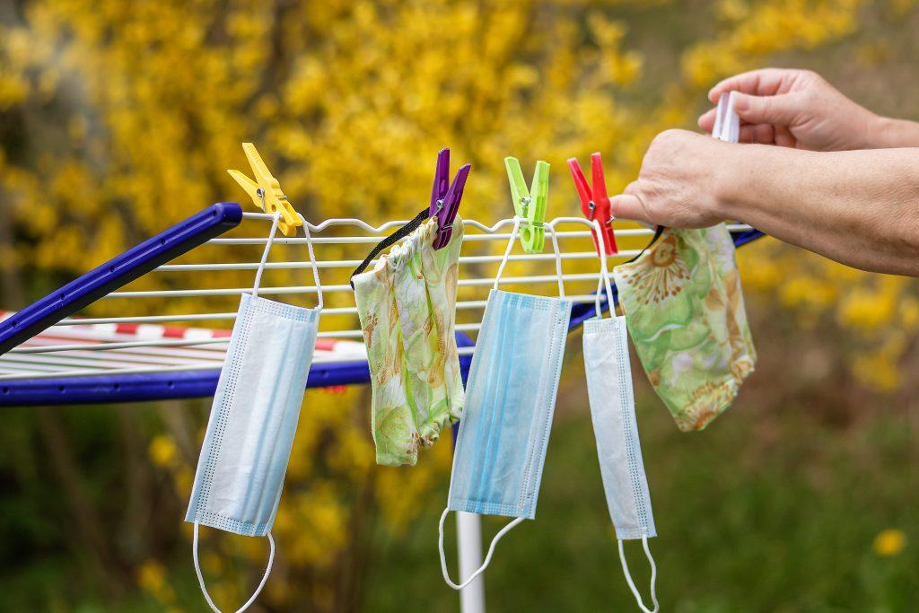 Pyykkitelineeseen ripustetaan kuivumaan kasvomaskeja.