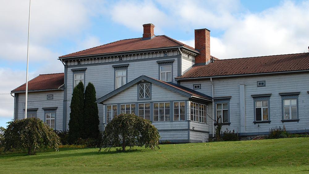 Valkoinen kartano on kuvattu takapihan puolelta, jossa on talon suuri lasiveranta. Etualalla on nurmikkoa ja omenapuita.