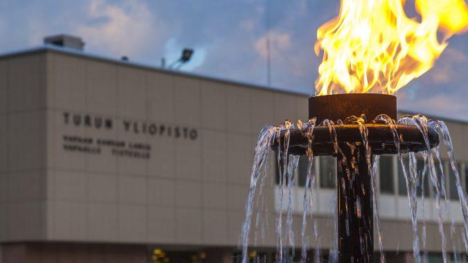 Kuvituskuvassa suihkulähteessä ulkotuli, taustalla yliopiston päärakennus