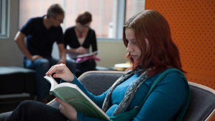 Kuvituskuvassa aikuisopiskelija lukee kirjaa