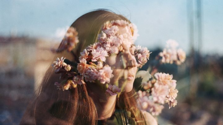 Kuvituskuvassa kaksoivalotuksella henkilön kasvot ja kukkia