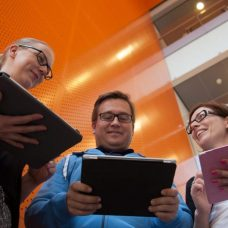 Aikuisopiskelijoita katsomassa tabletteja
