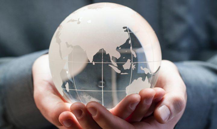 käsissä lasinen maapallon pienoismalli