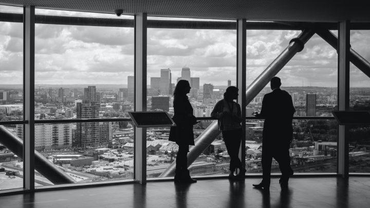 Kolme henkilöä pilvenpiirtäjän ikkunan edustalla