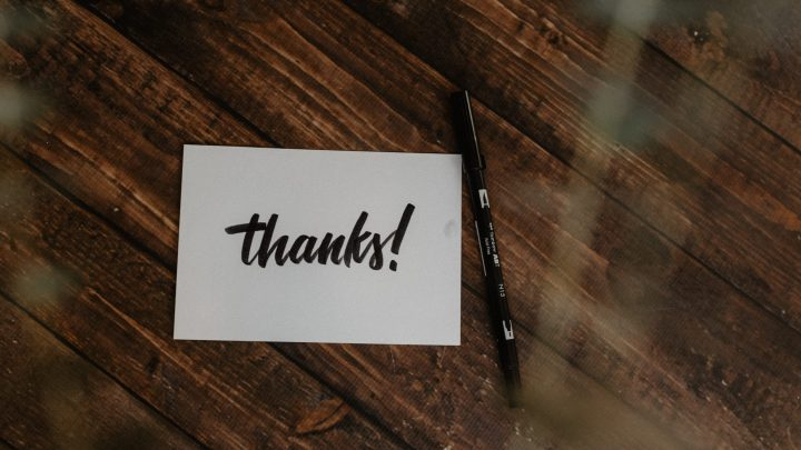 """Pöydällä kynä ja paperi, jossa lukee """"Thanks!"""""""