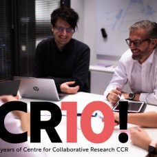 """Neljä CCR-yksikön työntekijää pöydän äärellä. Graafisessa tekstielementissä lukee """"CCR10! Celebrating 10 years of Centre for Collaborative Research CCR"""""""
