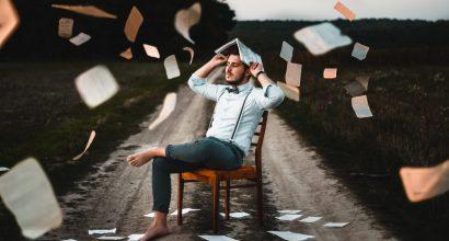 """Kuvituskuvassa henkilö istuu tuolilla autotiellä ja ympärillä """"sataa"""" kirjoja ja paperiarkkeja"""