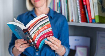 """Henkilö pitelemässä kirjaa jonka kannessa teksti """"Opettajana yliopistossa"""""""